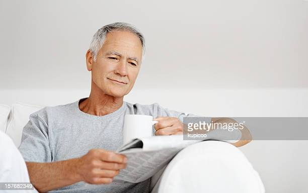 Mature male reading newspaper while holding cup of tea