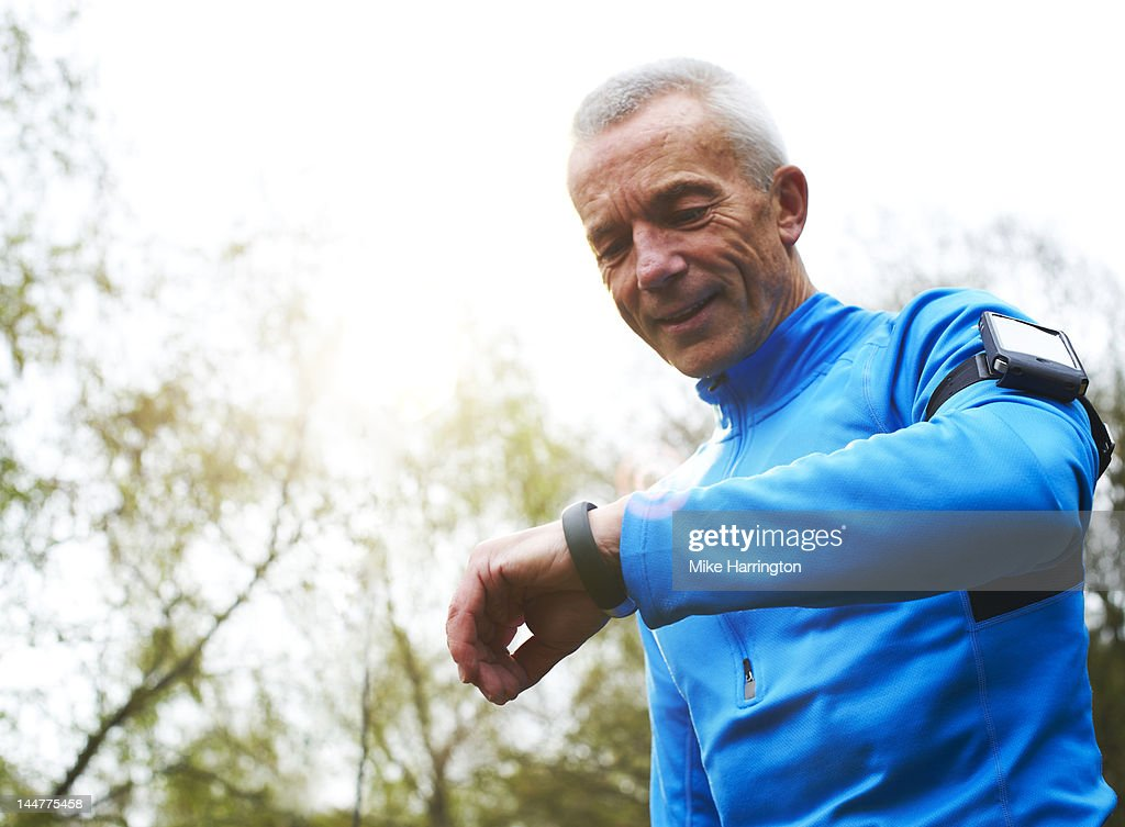 Mature Male Runner Looking at Digital Sports Band : Stock Photo
