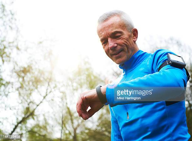 Mature Male Runner Looking at Digital Sports Band