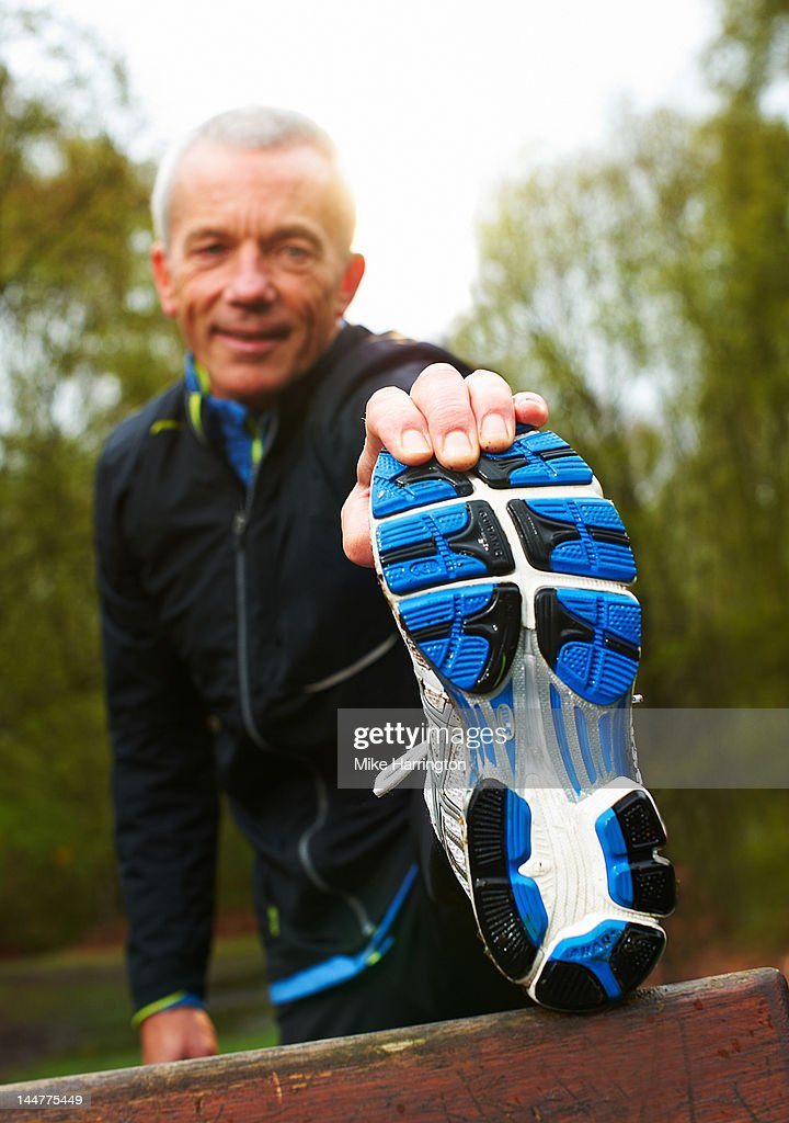 Mature Male Runner Stretching In Park : Stock Photo