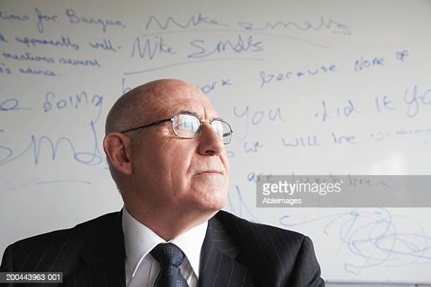 Mature male schoolteacher in front of whiteboard, close-up