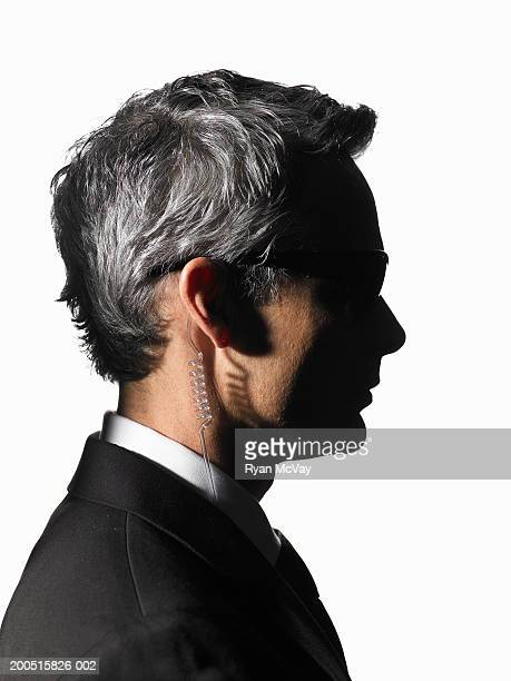 Mature male secret service agent wearing hands-free device, side view