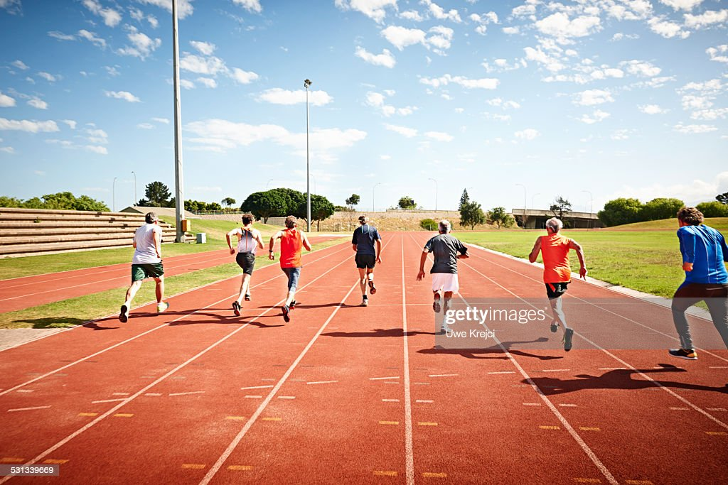 Mature male sprinters on running track