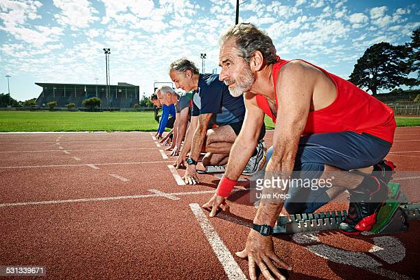 Mature male sprinters on starting blocks