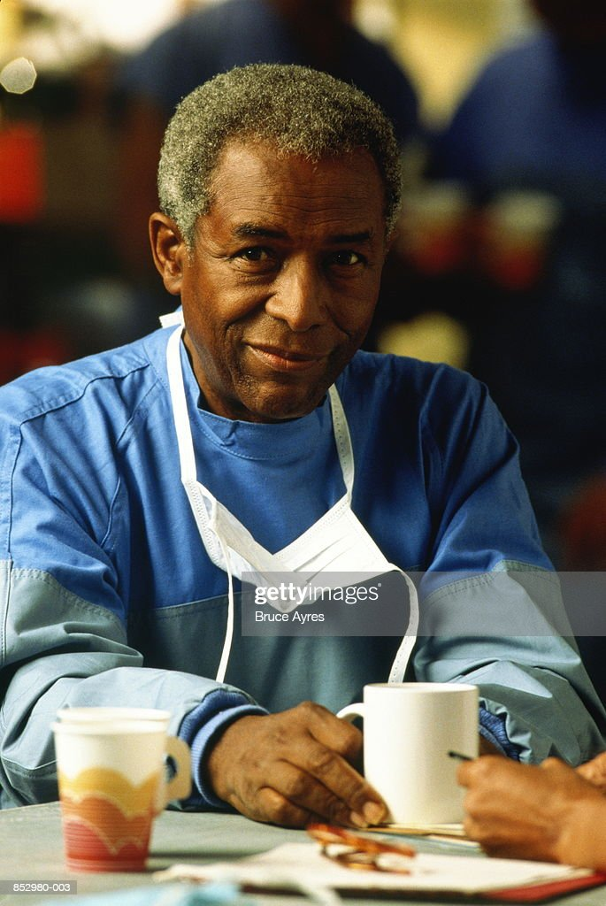 Mature male surgeon sitting, relaxing in canteen, portrait : Stock Photo