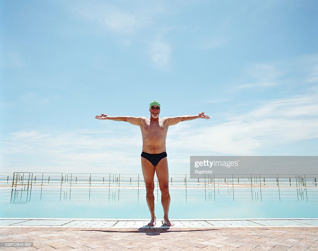 Mature male swimmer, arms outstretched, portrait