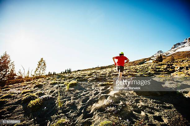 Mature male trail runner running up mountain