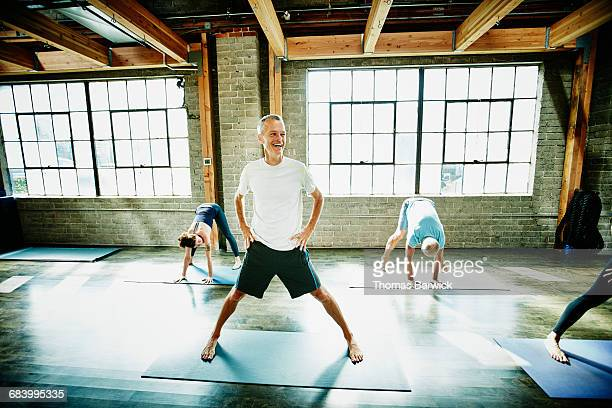 Mature male yoga student laughing during class