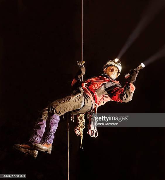 Mature man abseiling in cave, holding torch
