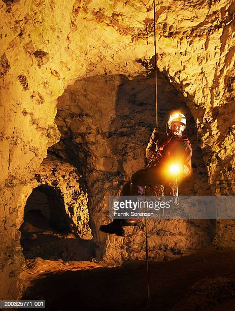 Mature man abseiling in cave, holding torch, portrait