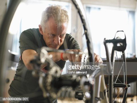 Mature man adjusting bicycle chain