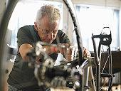 Mature man adjusting bicycle chain