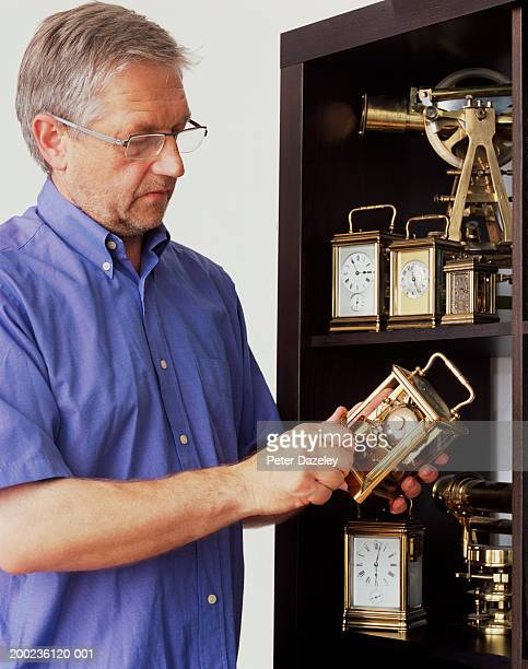 Mature man adjusting clock by cabinet containing many clocks