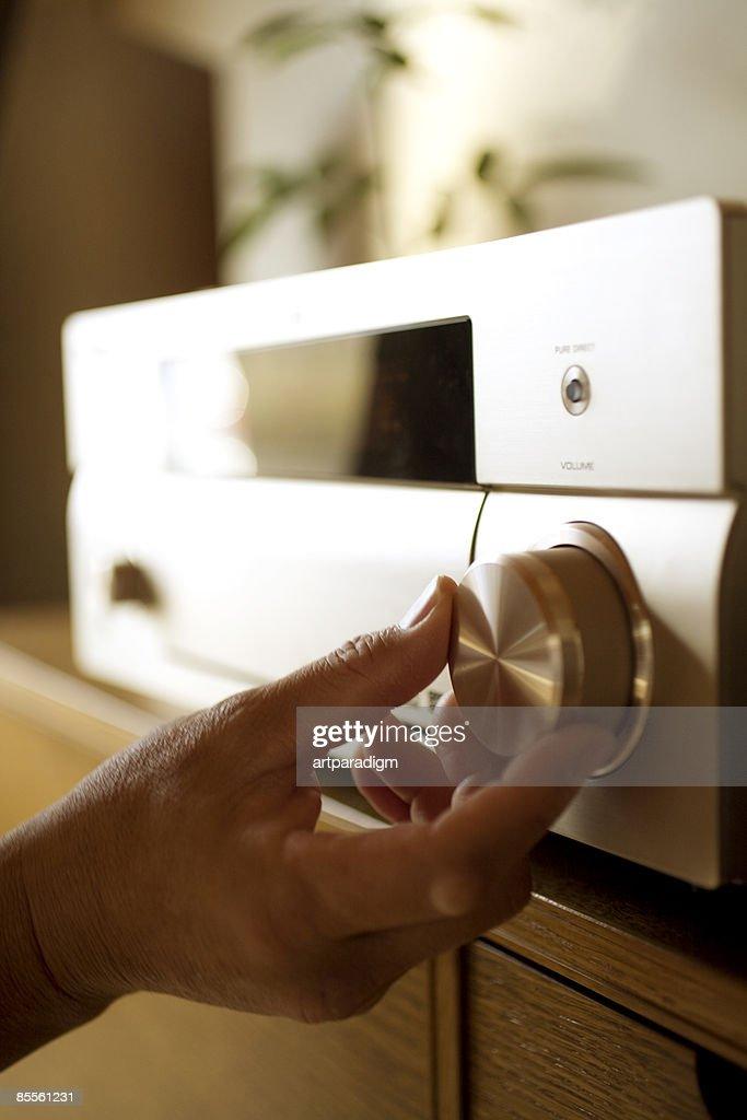 A mature man adjusting stereo
