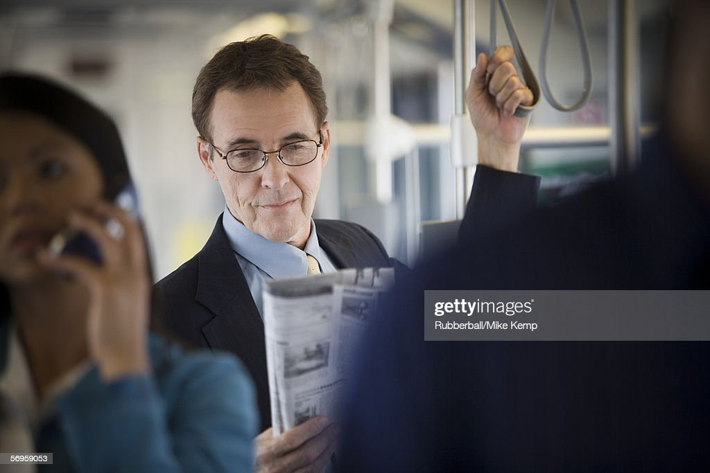 Mature man and a woman standing on a commuter train