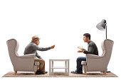 Mature man and a young guy seated in armchairs arguing isolated on white background