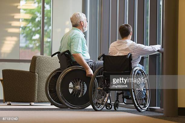 Mature man and a young woman sitting in wheelchairs in a library