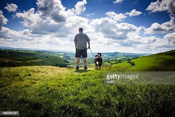 Reifer Mann und Hund in walisische Landschaft