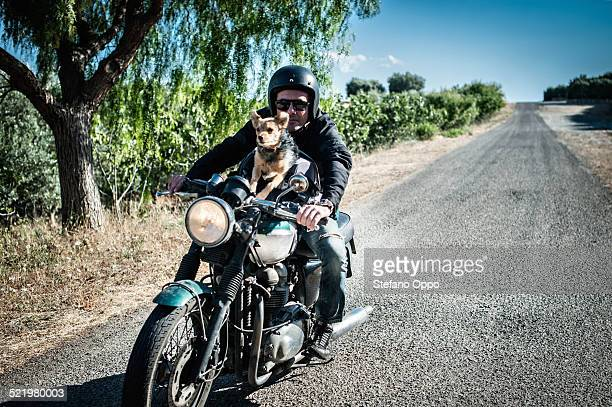 Mature man and dog riding motorcycle on rural road, Cagliari, Sardinia, Italy