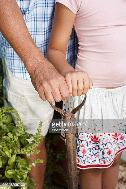 Mature man and granddaughter (6-8) leaning on spade, close-up