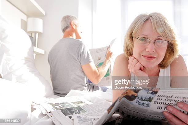Mature man and lady reading newspapershe papers