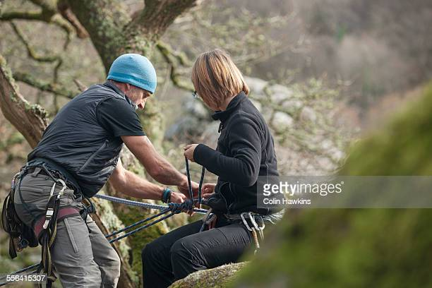 Mature man and mid adult woman putting on climbing ropes