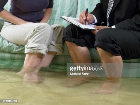 Mature man and mid adult woman sitting on sofa with water over their ankles, low section