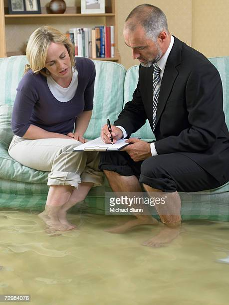Mature man and mid adult woman sitting on sofa with water over their ankles