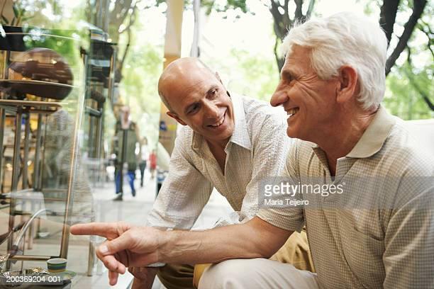 Reifer Mann und senior Mann kniend durch shop Fenster, Lächeln
