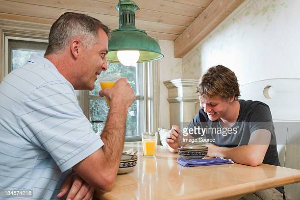 Mature man and son sitting together over breakfast