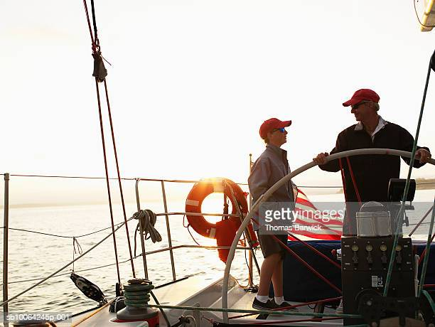 Mature man and teenage boy (13-14) on sailboat, man steering