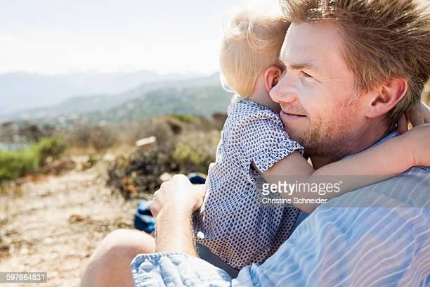 Mature man and toddler daughter hugging, Calvi, Corsica, France