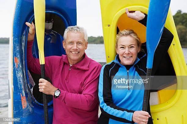 Mature man and woman carrying kayaks
