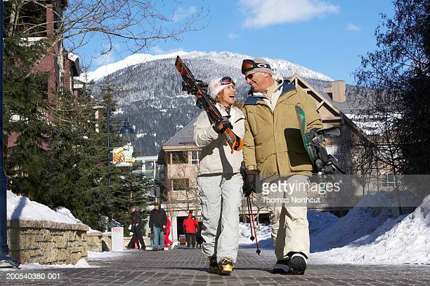 Mature man and woman carrying skis and snowboard, laughing