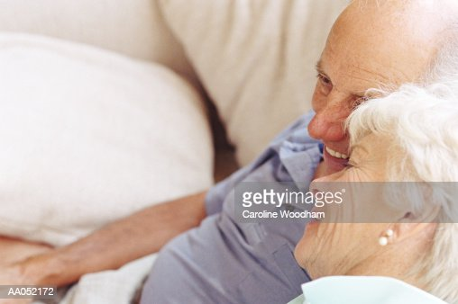 Mature man and woman cuddling on sofa, smiling, elevated view : Stock Photo