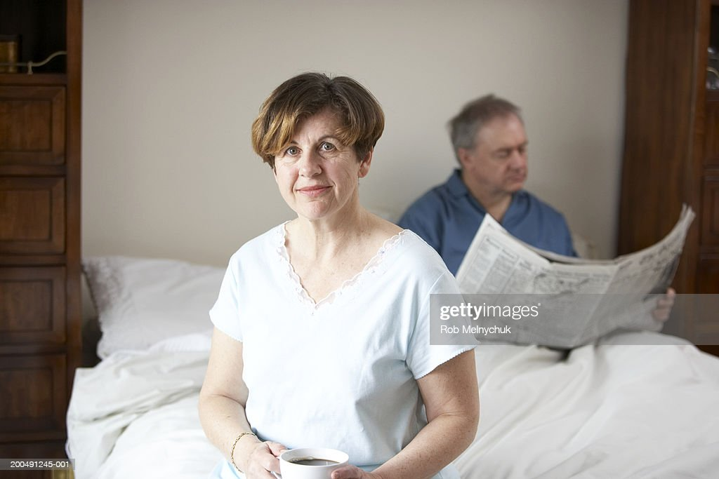 Mature man and woman drinking coffee and reading newspaper in bed : Stock Photo