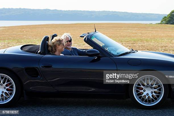Mature Man and Woman driving in open car