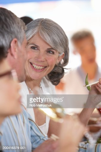 Mature Man And Woman Eating In Restaurant Smiling At One