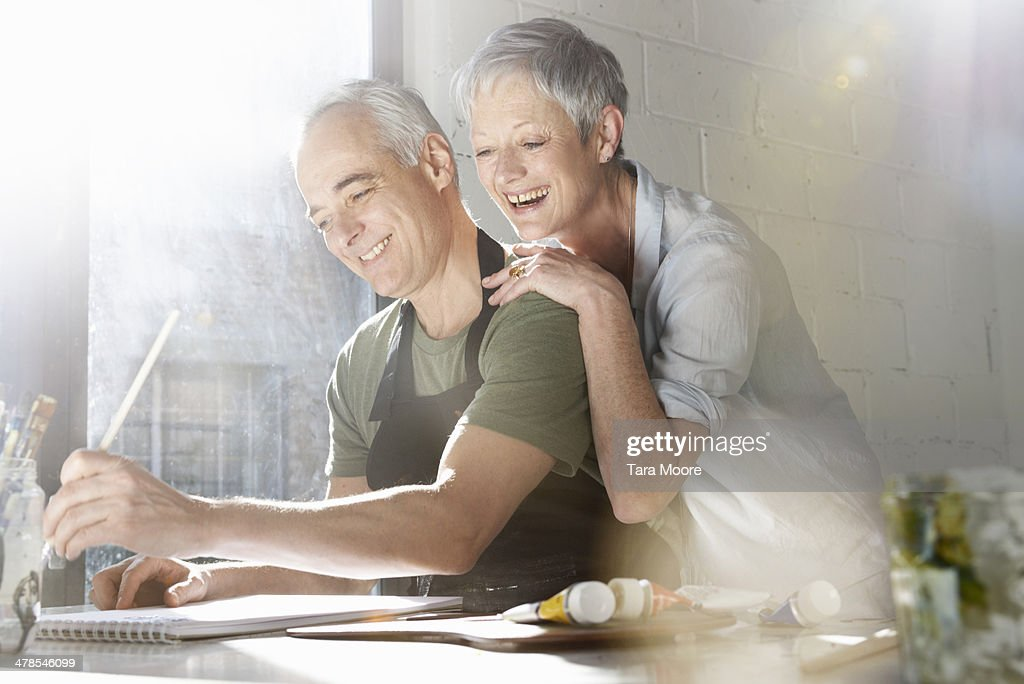 mature man and woman in artist studio : Stock Photo