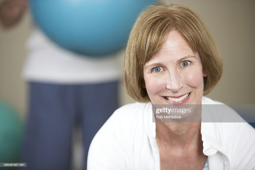 Mature man and woman in gym (focus on woman smiling in foreground) : Stock Photo