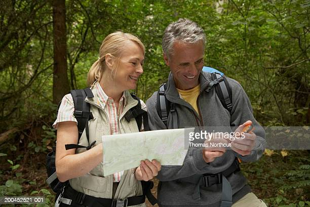 Mature man and woman looking at map and using GPS in forest