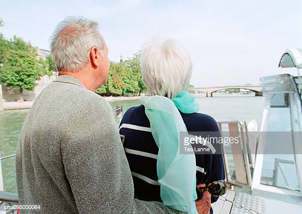 Mature man and woman on a barge, rear view