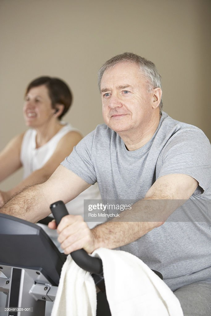 Mature man and woman on exercise bikes (focus on man in foreground) : Stock Photo