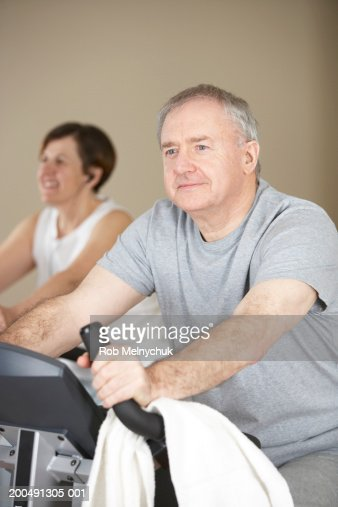 Mature man and woman on exercise bikes (focus on man in foreground) : Foto de stock