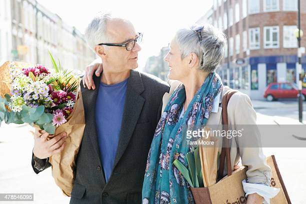 mature man and woman on street with shopping