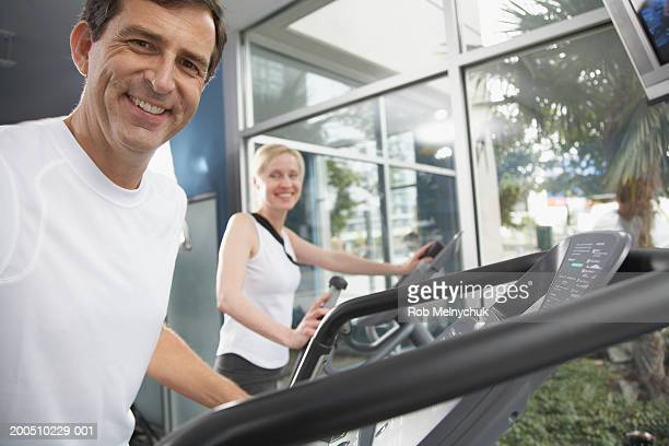 Mature man and woman on treadmills (focus on man in foreground)