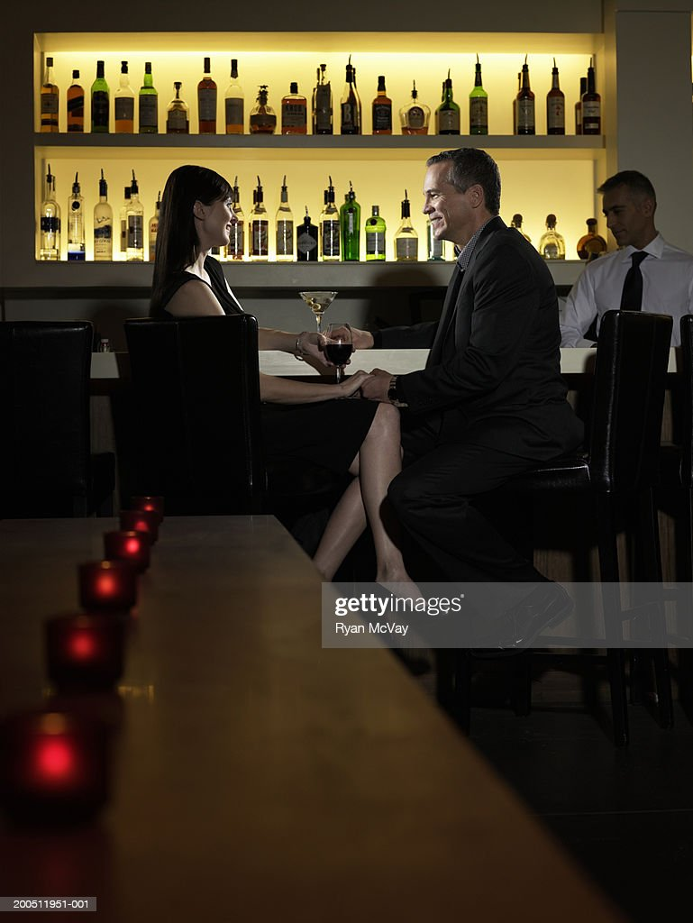 Mature man and woman sitting at bar counter, talking and holding hands : Stock Photo