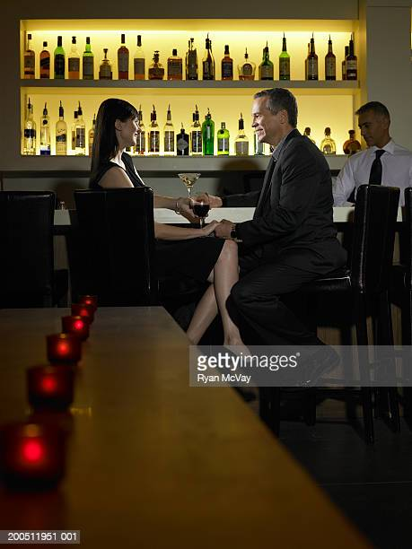 Mature man and woman sitting at bar counter, talking and holding hands