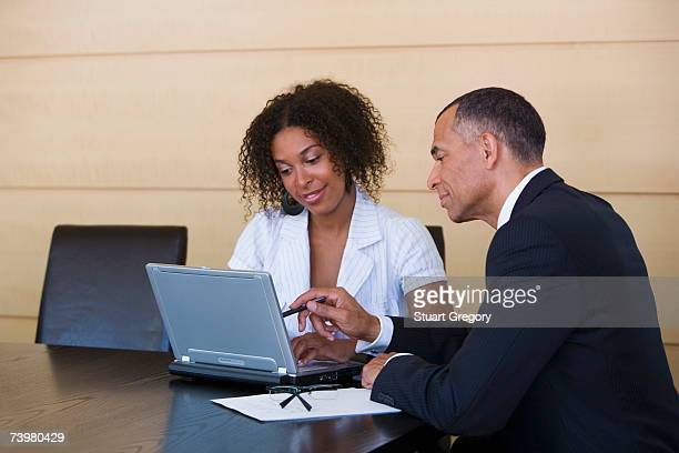 Mature man and woman sitting at conference table, smiling