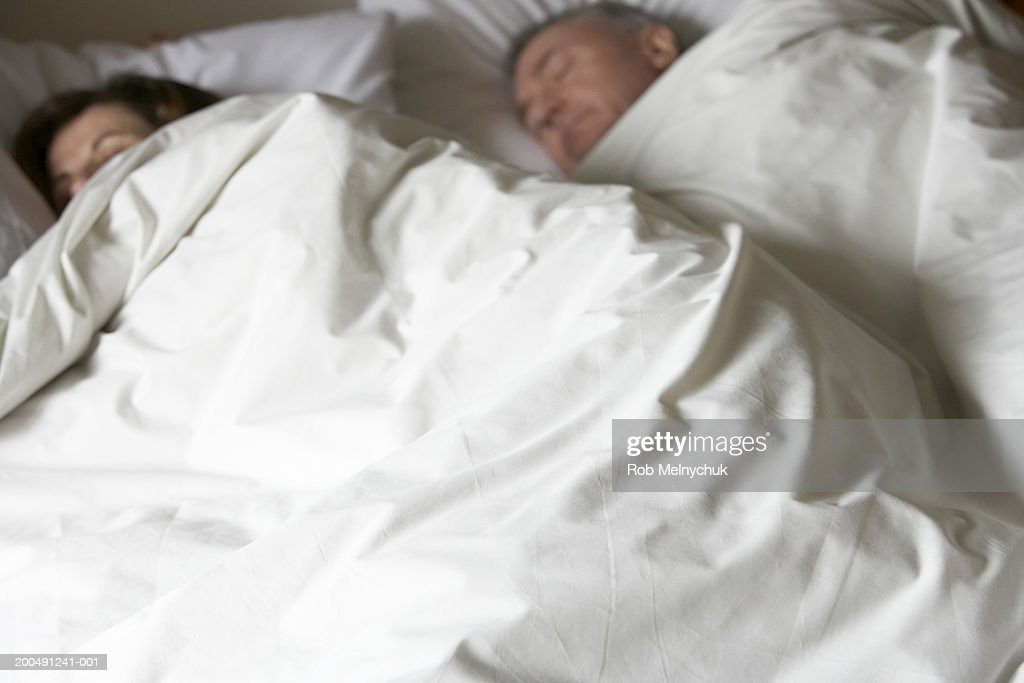 Mature man and woman sleeping in bed, elevated view : Stock Photo